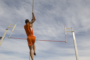 Low angle view of a male athlete performing a pole vault against the sky