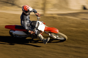 Male off road biker riding the motor bike with speed on a race track