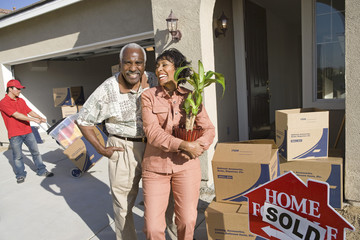 Cheerful African American couple with belongings moving into a new house