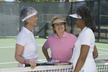 Three senior female tennis player having a friendly chat in court