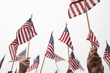 Hands raising American flags against clear sky