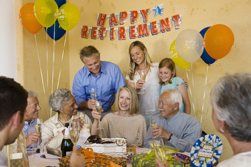 Happy senior couple celebrating retirement party with friends and family