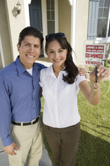 Portrait of a Hispanic couple holding keys of their new house