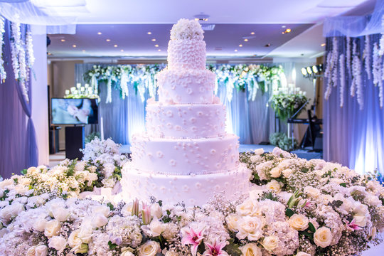 A beautiful wedding cake with decoration at wedding reception room for wedding party. Beautiful Cakes dessert and flower decorate in event party room. White Cake Design in Wedding Room with blue light