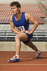 Full length of confident male athlete stretching in racing field
