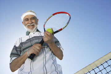 Low angle view of a happy senior man holding tennis racquet and ball against sky