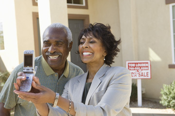 Cheerful African American couple taking self-portrait through cell phone in front of new house