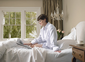Relaxed woman in shirt reading newspaper on bed