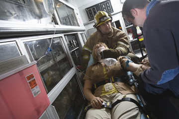 Firefighter and EMT doctor helping an injured woman in ambulance