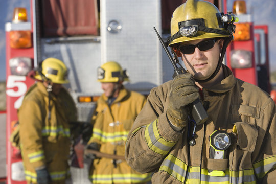 Portrait of a middle aged firefighter talking on radio with colleagues standing in the background