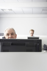Middle aged businessman on call at computer desk with colleague in background