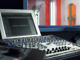 Closeup of mixing deck and monitor in recording studio