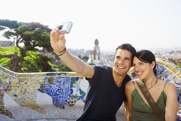 Young couple taking self portrait while sitting on stone bench at Barcelona