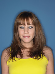 Closeup of a cross eyed woman in yellow tank top against blue background