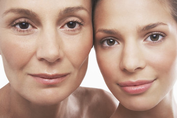 Closeup portrait of two beautiful women smiling on white background