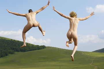 Full length rear view of naked young couple with arms outstretched jumping in park