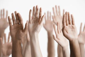 Closeup of multiethnic men and women raising hands against white background