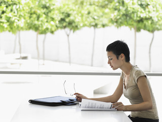 Side view of young businesswoman reading book at desk in office