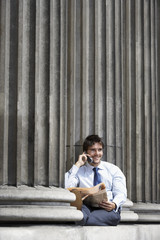 Portrait of smiling young businessman using mobile phone between pillars