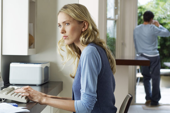 Side view of a worried young woman using computer at home