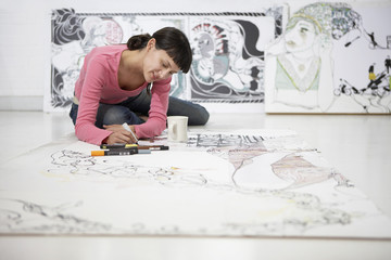 Young female artist drawing on large paper at home office