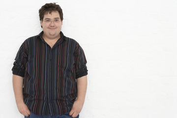 Portrait of an overweight young man standing against white background