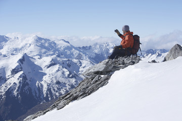 Male climber taking picture of snowy mountains on peak