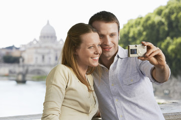 Happy young couple photographing selves with digital camera in Rome, Italy