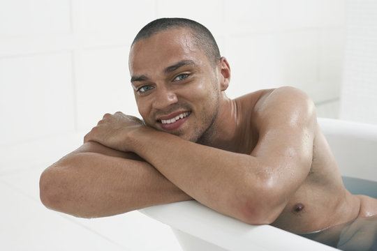 Closeup of a smiling man relaxing in a bathtub at home