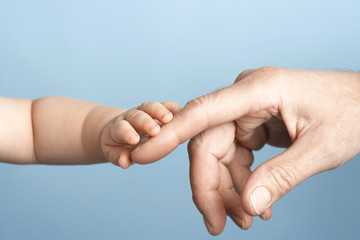 Closeup of a baby holding man's finger against blue background