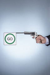 Man's hand firing pistol with go flag over colored background