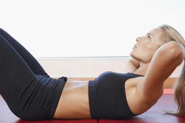 Side view of sporty young woman doing sits-up at gym