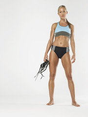 Full length portrait of a female athlete holding shoes against white background