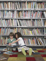 Full length of young boy and girl with picture books in library