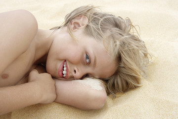 Portrait of playful little boy lying on sand at beach