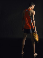 Full length rear view of a male athlete holding shoes against black background