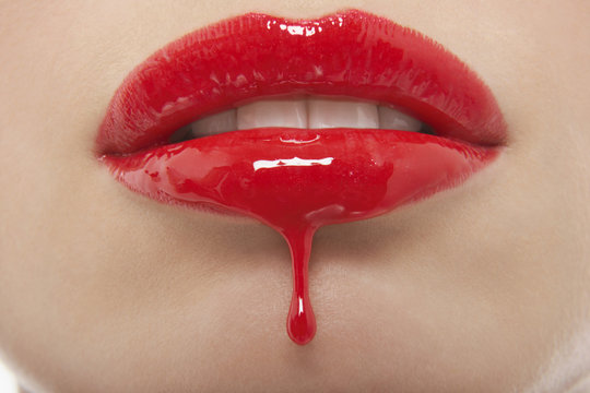 Detail shop of red lipgloss dripping from woman's lips