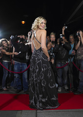 Full length of attractive female celebrity on red carpet in front of fans and paparazzi