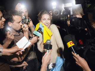Excited middle aged female cleaner surrounded by paparazzi
