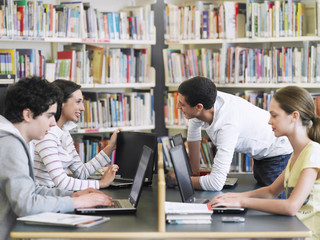 Teenage students using laptops in library