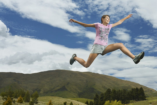 Low angle view of a young woman leaping on rural landscape