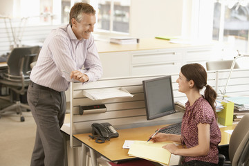 Happy businessman discussing with female colleague at cubicle