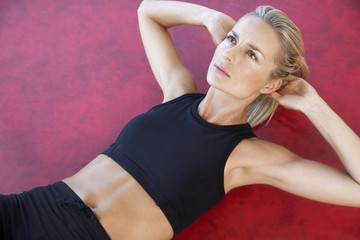 Fit young woman in sportswear doing sits-up on floor