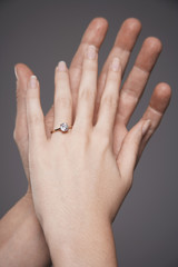 Closeup of hands together showing woman's engagement ring against gray background