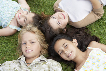 High angle view of friends with their head together lying on grass