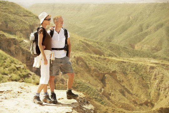Full length of hiking couple standing on top of mountain