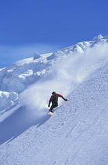 Snowboarder snowboarding on steep slope
