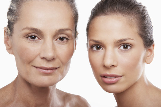 Closeup portrait of two women of different ages on white background