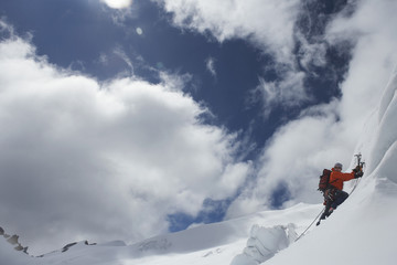 Side view of a male mountain climber going up snowy slope with axes against clouds