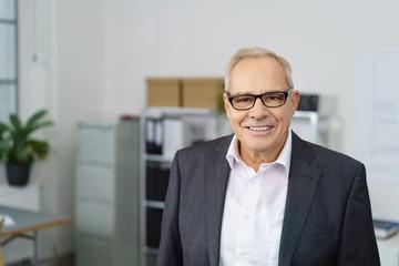 älterer geschäftsmann mit brille im büro